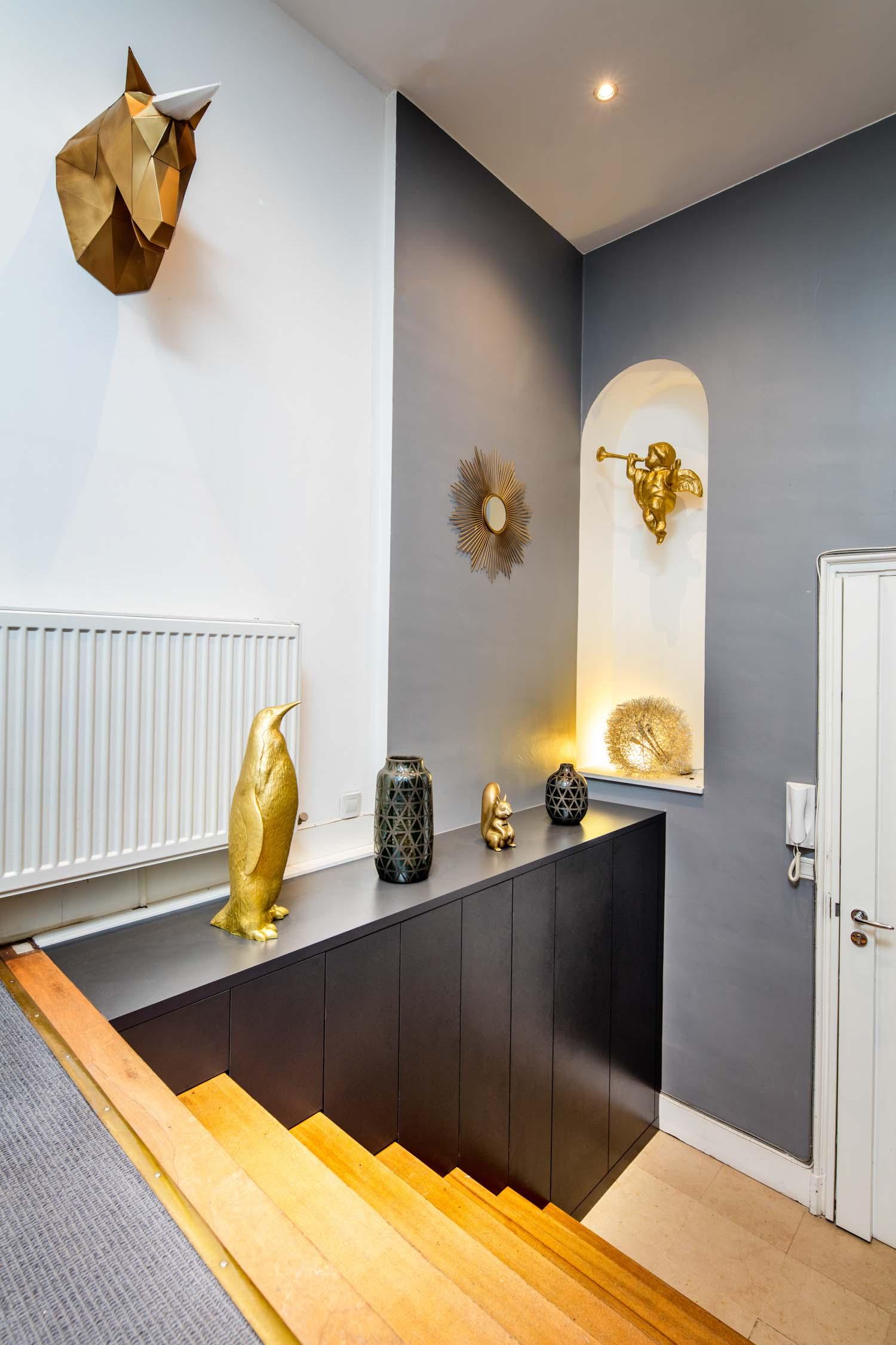 Placard meuble noir ajusté à la forme de l'escalier d'entrée