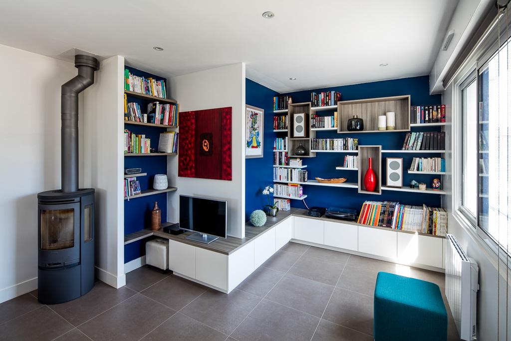 Bibliothèque, meuble TV et de rangements fermés reprenant le relief des murs du salon