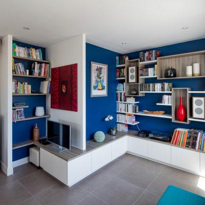 Bibliothèque, meuble TV et de rangements fermés reprenant le relief des murs du salon - vue de droite