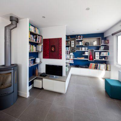 Bibliothèque, meuble TV et de rangements fermés reprenant le relief des murs du salon - vue de face