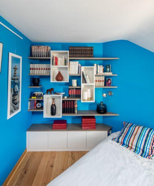 Bibliothèque dans une chambre, avec des caissons suspendus blancs et des étagères en effet chêne