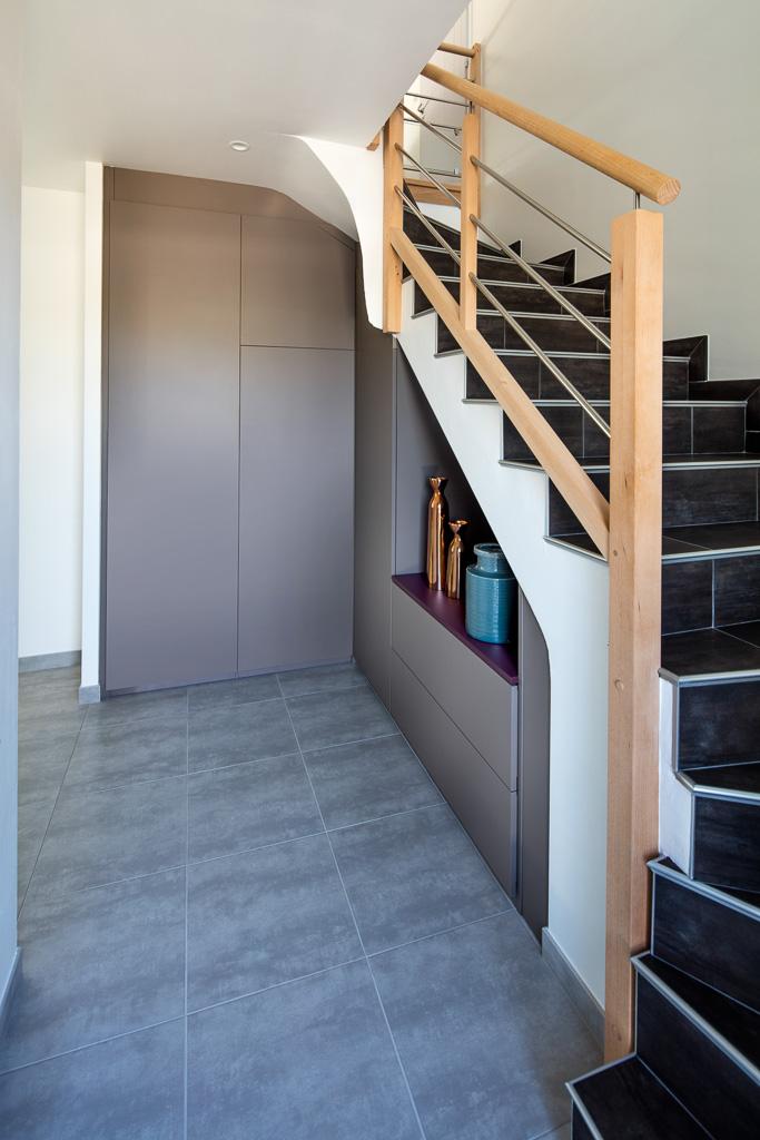 Placard sous-escalier sur-mesure taupe avec une niche et une jolie découpe - vue de droite et portes fermées