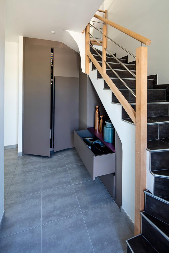 Placard sous-escalier sur-mesure taupe avec une niche et une jolie découpe - vue de droite et portes ouvertes