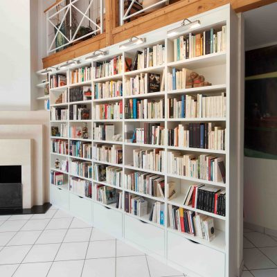 Bibliothèque blanche autour d'une cheminée