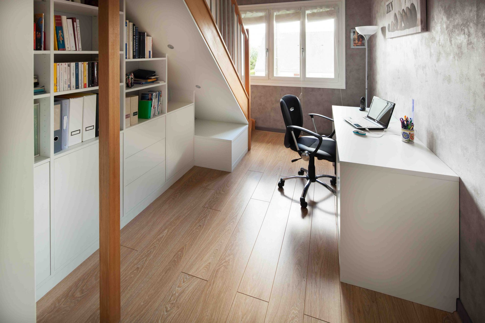 Bureau blanc aménagée à côté d'un escalier