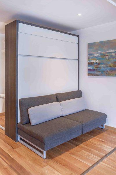 Lit rabattable en bois foncé avec canapé