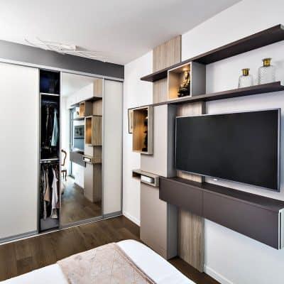 chambre design avec meuble TV et dressing sur-mesure avec ses portes sur coulisses ouvertes