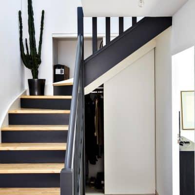 rangement blanc sous-escalier avec miroir ouvert côté gauche